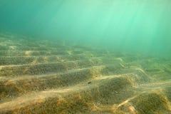 A foto subaquática, areia pequena 'dunas 'disparou diagonalmente assim nesta perspectiva que formam escadas, raios do sol que vêm imagens de stock royalty free