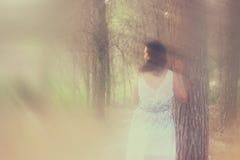 A foto surreal da jovem mulher que está na imagem da floresta textured e é tonificada Conceito sonhador Foto de Stock Royalty Free
