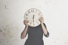 Foto surreale di una donna che si nasconde dietro un grande orologio fotografia stock