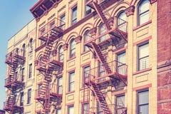 Foto tonificada retro do filme velho da construção de New York com escape de fogo imagens de stock
