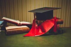 Foto tonificata del cappuccio rosso di graduazione e del nastro sulla tavola classica Fotografia Stock Libera da Diritti
