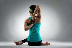 Foto trasera de la visión de la mujer de la aptitud que hace la presentación de la yoga Imágenes de archivo libres de regalías
