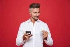 Foto van de glimlachende mens in de witte creditcard van de overhemdsholding en smar stock afbeelding