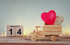 Foto van 14 de houten uitstekende kalender van Februari met houten stuk speelgoed vrachtwagen met harten voor bord Stock Foto's