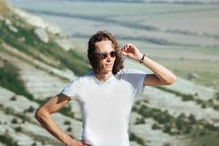 Foto van de jonge knappe ernstige zich over bergen bevinden en mens die opzij kijken Royalty-vrije Stock Foto's
