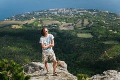 Foto van de jonge knappe ernstige zich over bergen bevinden en mens die opzij kijken Royalty-vrije Stock Afbeeldingen