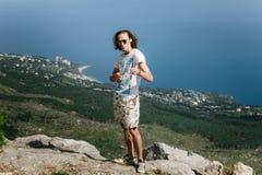 Foto van de jonge knappe grappige mens die zich over bergen bevinden en camera bekijken Stock Foto