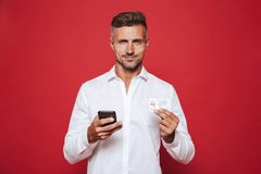 Foto van de knappe mens in de witte creditcard en sma van de overhemdsholding stock foto