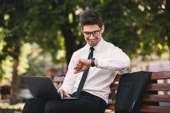 Foto van de knappe mens in zakelijk kostuum die aan laptop binnen werken stock afbeeldingen