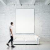 Foto van de mens in galerij Wachings het lege canvas hangen op de bakstenen muur en de uitstekende klassieke bank houten vloer vi royalty-vrije stock fotografie