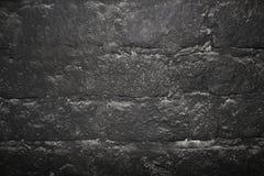Donkere de textuurachtergrond van de steenmuur Stock Foto's