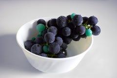 Foto van donkere violette druiven in een kop stock afbeelding