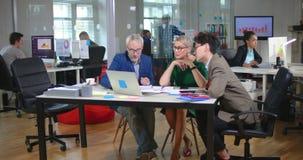 Foto van drie ontwerpers die bij bureau in bureau zitten stock videobeelden