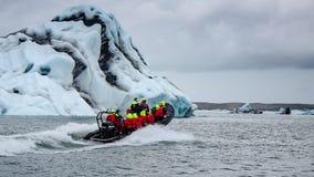 Foto van een boot die de blauwe enorme ijsberg naderen stock fotografie