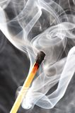 Foto van een brandende gelijke in een rook op een zwarte achtergrond Royalty-vrije Stock Foto's