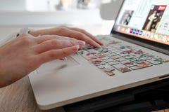 Foto van een close-up van vrouwen` s handen die aan laptop binnen een huis werken royalty-vrije stock afbeelding
