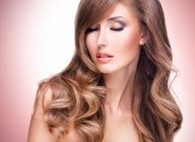 Foto van een mooie vrouw met lang bruin haar en heldere makeu stock afbeeldingen