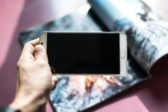 Foto van een tijdschrift met een camera op een smartphone wordt genomen die Stock Fotografie