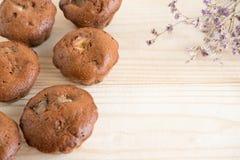 Foto van eigengemaakte muffins met droge bloemen op houten achtergrond Eigengemaakt baksel Chocolademuffins met bananen Chocolade royalty-vrije stock fotografie