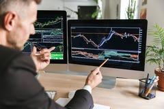 Foto van ernstige zakenmanzitting bij lijst in bureau en het werken met grafiek en grafieken aan computer royalty-vrije stock afbeelding