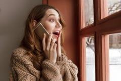 Foto van Europese vrouwenjaren '20 met bruin haar die op mobiele ph spreken Stock Fotografie