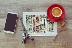 Foto van gebouwen in Parijs op houten lijst met koffiekop en slimme telefoon Mening van hierboven Stock Afbeelding