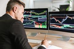 Foto van geconcentreerde zakenmanzitting bij lijst in bureau en het werken met grafiek en grafieken aan computer stock fotografie