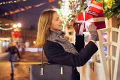 Foto van gelukkig brunette met glas in handen dichtbij dozen met giften stock afbeelding