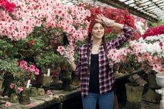 Foto van gelukkige jonge vrouwentuinman in een plaidoverhemd die kleine spade met roze en rode yard op de achtergrond houden royalty-vrije stock afbeeldingen