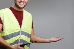 Foto van glimlachende bouwer in geel vest met opgeheven omhoog palm royalty-vrije stock afbeeldingen