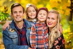 Foto van glimlachende familie met kinderen op gang in de herfstpark stock fotografie