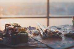 Foto van gouache en waterverf met borstels in kunststudio die worden geplaatst Olieverven op palet worden gesmeerd dat Stock Fotografie