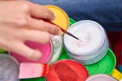 Foto van hand met een borstel, buizen van verf, het proces van tekening stock fotografie