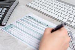 Foto van handen die en de belastingsvorm van de V.S. naast computertoetsenbord, dollarrekeningen en belastingsvorm 1040 berekenen stock fotografie
