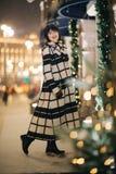 Foto van het brunette van gemiddelde lengte in straat op vage achtergrond royalty-vrije stock afbeelding