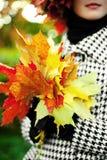 Foto van het charmeren van vrouw met esdoornbladeren royalty-vrije stock afbeeldingen