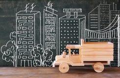 Foto van houten stuk speelgoed vrachtwagen voor bord met stadsillustratie Royalty-vrije Stock Foto