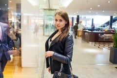 Foto van jonge blije vrouw met handtas op de achtergrond van sh Stock Afbeeldingen