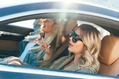 Foto van kant van blonden die zonnebril dragen terwijl het drijven in auto royalty-vrije stock afbeeldingen