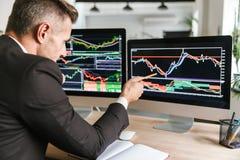 Foto van Kaukasische zakenmanzitting bij lijst in bureau en het werken met grafiek en grafieken aan computer royalty-vrije stock fotografie