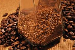Foto van koffiebonen en glaskruik met onmiddellijke koffie op bruine achtergrond Royalty-vrije Stock Afbeelding