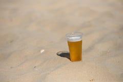 Foto van koud bier in het hete zand Dalingen van water op glas Thi Stock Foto
