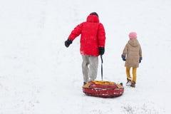 Foto van lopende vader met buizenstelsel, dochter op de winterpark stock afbeeldingen