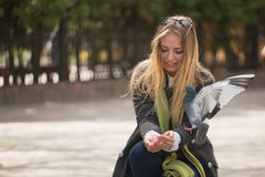 Foto van Meisje en duiven Voedende duiven in het park stock afbeelding