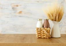 Foto van melk en chocolade naast tarwe over houten lijst en witte achtergrond Symbolen van Joodse vakantie - Shavuot royalty-vrije stock afbeeldingen