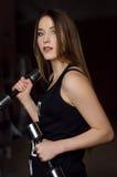 Foto van mooie jonge vrouw met lang haar en domoren bij de gymnastiek Stock Fotografie