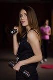 Foto van mooie jonge vrouw met lang haar en domoren bij de gymnastiek Stock Afbeeldingen