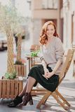 Foto van mooie rode haired vrouw de gekleed in modieuze kleren, zit in openlucht, stelt bij cafetaria, heeft prettige verschijnin royalty-vrije stock foto