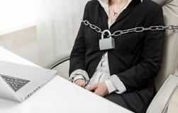 Foto van onderneemster aan stoel door metaalketting die wordt gebonden stock afbeelding