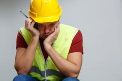 Foto van ongelukkig bouwersmannetje in gele helm met walkie-talkie stock afbeeldingen